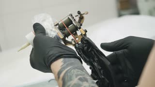 The tattooist checks the tattoo machine for perfomance before the tattoo session