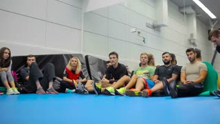The team of young people sits on floor in the gym on the training