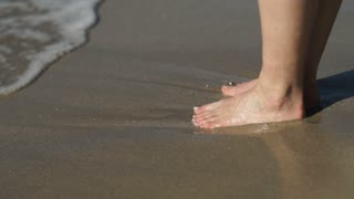 The waves washes female's feet