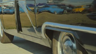 The woman in silver shoes comes out from retro car