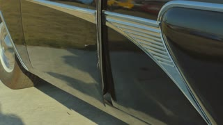 The woman in silver shoes on high heels comes out from retro car