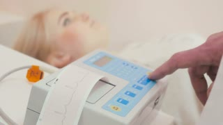 The woman makes a electrocardiogram in doctor's office