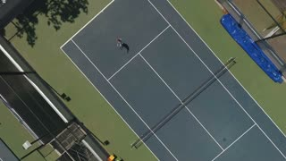 The woman plays tennis at the court