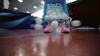 The woman pour tennis balls out of the box at the floor
