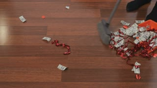 the woman sweeping with a broom dollars and confetti on a wooden floor