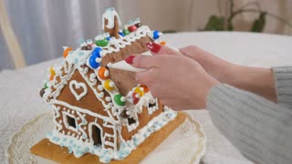 The woman writes a text with cream on the roof of gingerbread house