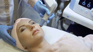 Therapist makes rf-lifting procedure of facial skin