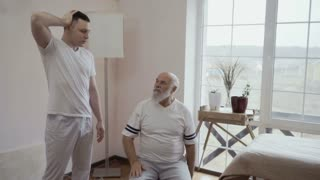 Therapist show a sport exercise to old man