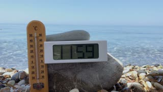Thermometer show the temperature of air at midday at the beach
