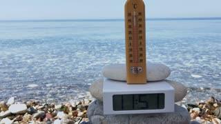 Thermometer with electronic clock at sea background