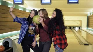 Three adult caucasian people makes selfie with bowling ball