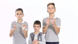 Three boys applauds at white background