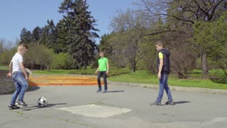 Three boys plays football in park, fourth boy riding on kick scooter