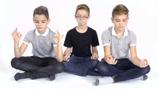 Three brothers meditating at white background