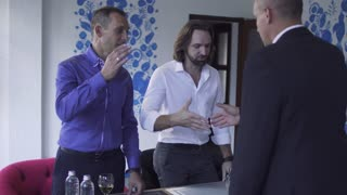 Three bussinessmen shake hands after successful meeting in restaurant