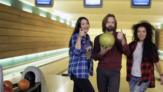 Three caucasian friends shows thumbs up standing at bowling alley
