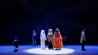 Three different girls sing song together on the stage in theatre
