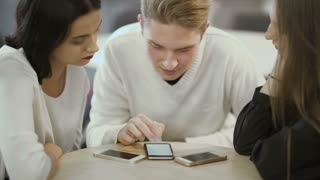 Three friends looks on the screen of smartphone