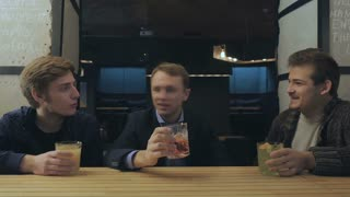 Three friends sits in a bar, relaxing and talking with each other