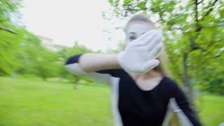 Three funny mimes imitate to turn camera