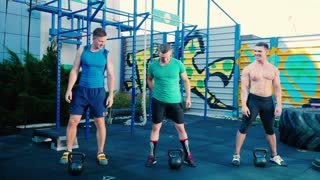 Three handsome sportsmen training with dumbbels at sports ground