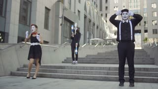 Three mimes have fun standing near office center