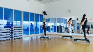 Three pretty woman make the exercises of step aerobics in front of mirror