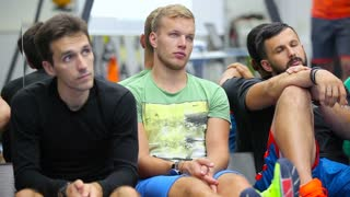 Three sports men sitting on the floor in the gym
