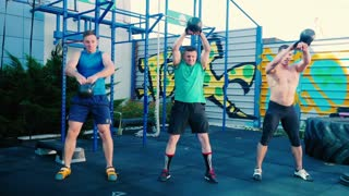 Three sportsmen raise up the dumbbels at the sports ground
