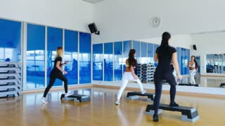 Three sporty young women training a step aerobics in the gym with step