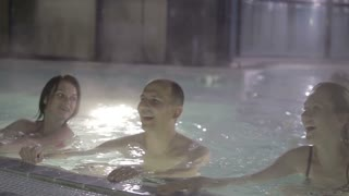 Three young people having fun in the pool