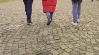 Three young people walking on pavers stones