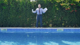Tired businessman throws documents and jumps in swimming pool in suit