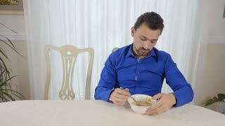 Tired man with bowl with corn flakes
