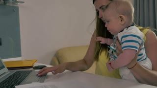 Tired mother works with laptop with baby in arms