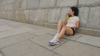Tired runner sits near stone wall and resting after training