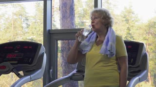 Tired senior woman drinks water in the gym