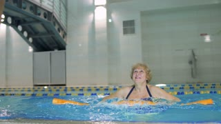 Trainer shows elderly woman fitness exercises in the swimming pool