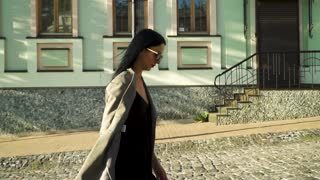 Trendy woman in sunglasses walking at the street in slow motion