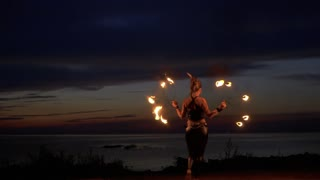 Tribal woman is spinning around with fire fans