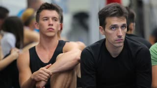 Two attractive men listening a coach on the training in the gym