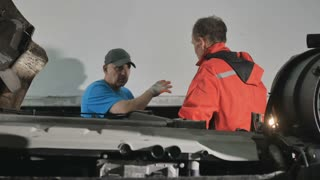 Two auto mechanics discuss details of repairing engine of truck