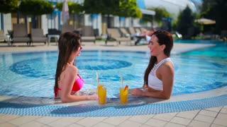 Two beautiful brunettes relaxing in the swimming pool with juice