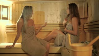 Two beautiful girlfriends relaxing in the sauna
