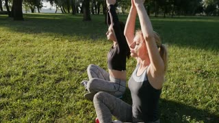 Two beautiful girls in sport leggings are sitting in the park.