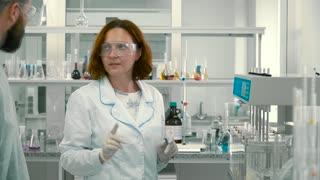 Two chemists talking in laboratory