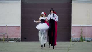 Two comic couples on stilts are dancing near the building