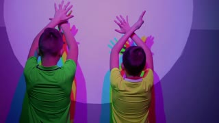 two cute boys shows thumbs up, colorful shadows on the wall