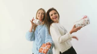 Two cute girls gives presents to each other at white background