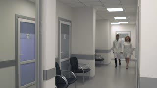 Two doctors walk along the corridor of the medical center and communicate